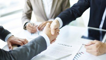 Two arms reaching across table to shake hands over a business agreement.