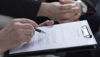 A couple holding hands and reading through a trust and probate document.