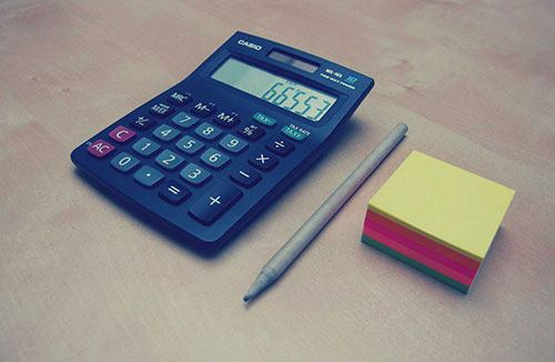 A handheld calculator, pen, and pad of paper on table top.