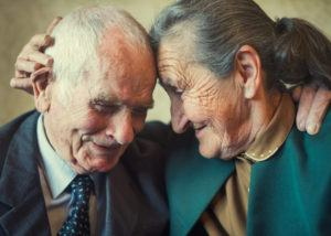 Elderly couple embracing one another endearingly.