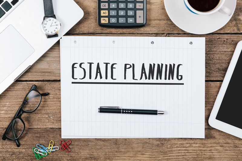 Estate planning preparation concept. Desktop with laptop, calculator, and notepad.