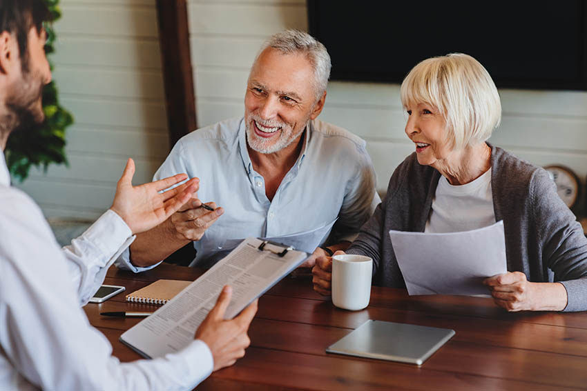 happy older couple discussing estate planning with their attorney