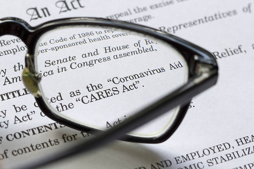Closeup of the Coronavirus Aid, Relief, and Economic Security Act documents laying on a desk with eye glasses