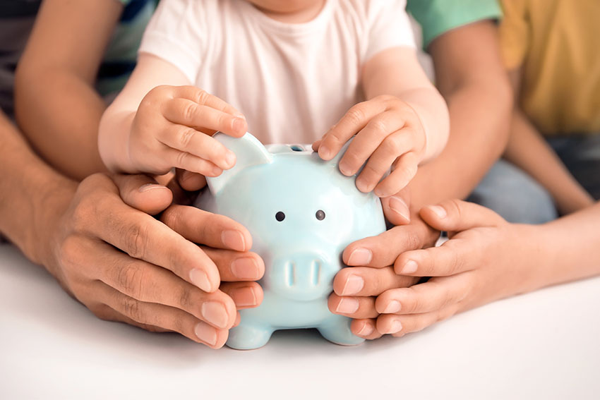 Family of three holding a piggy bank to symbolize family asset protection